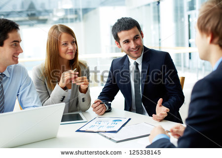 stock-photo-image-of-business-partners-discussing-documents-and-ideas-at-meeting-125338145