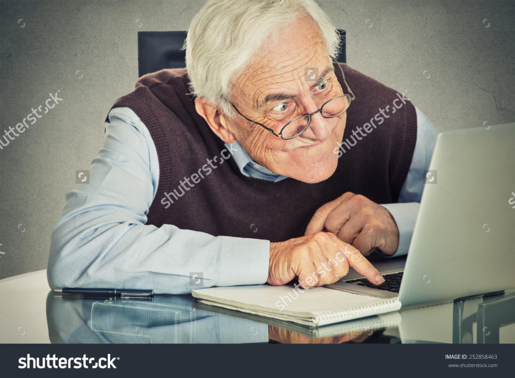 stock-photo-elderly-old-man-using-computer-sitting-at-table-isolated-on-grey-wall-background-senior-people-and-252858463