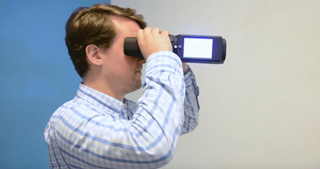 Un homme tient les binoculaires QuickSee devant ses yeux.