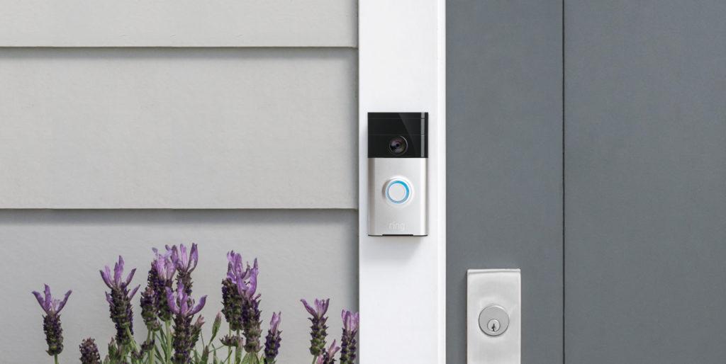 Photo d'une sonnette connectée Ring sur le pas d'une porte de maison.